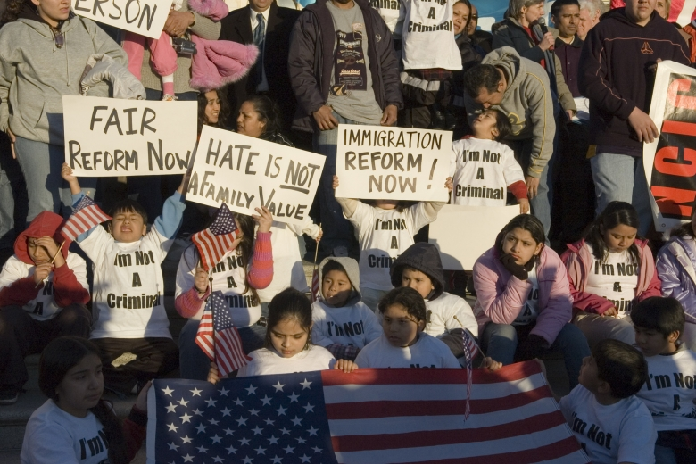 A multi-age group holds signs and a U.S. flag.