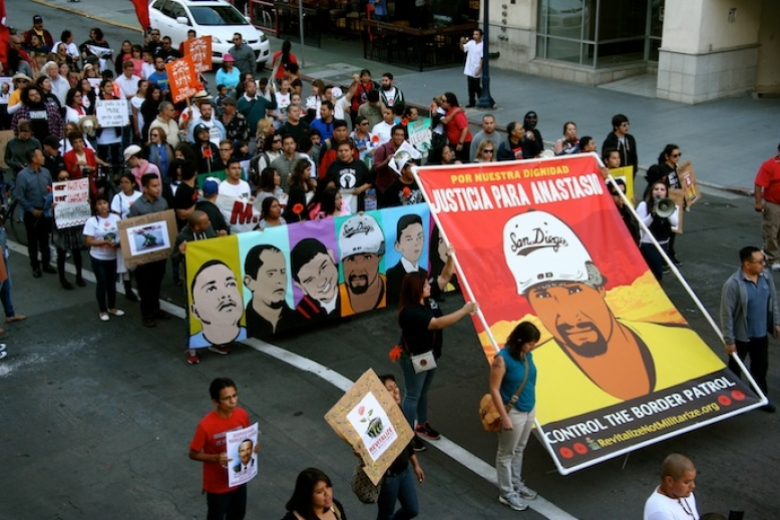 Large group of people march in street holding drawings of men who were killed by border patrol.