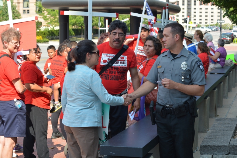Surrounded by other protesters, a woman shakes hands with a police officer.