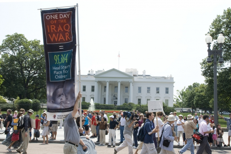Group of people march together in front of the White House, one person holding a sign referencing the cost of the Iraq War.