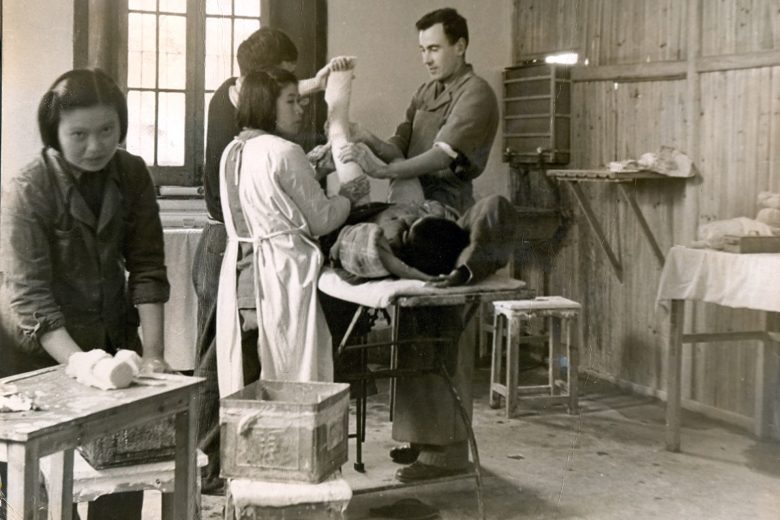Medical personnel examine a patient who is lying on a table, leg bent up in the air.