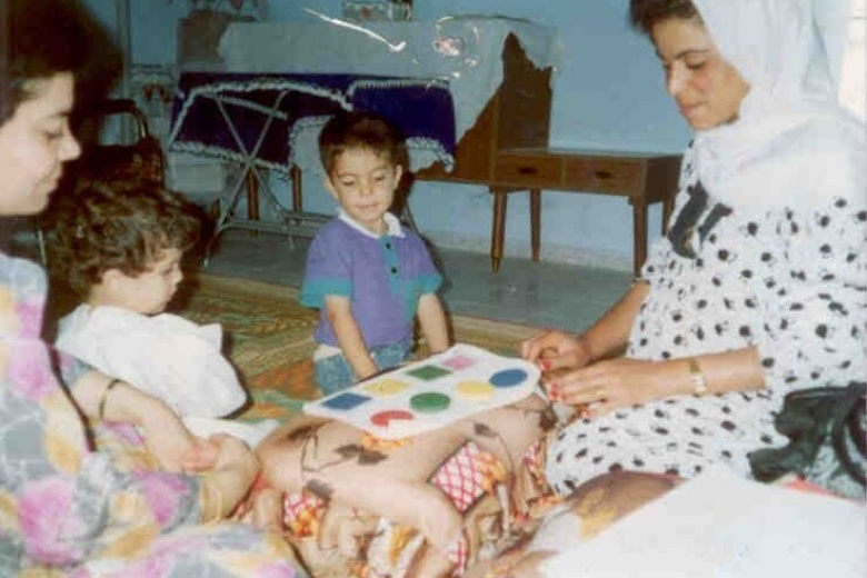 Two women sitting on the ground, playing with two children.