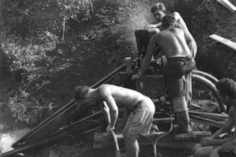 young men work with pipes and drilling equipment