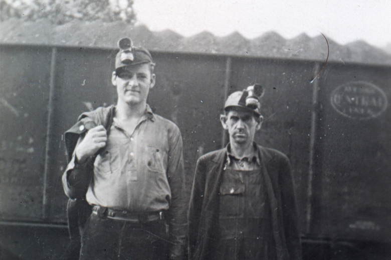 Two coal miners standing next to a train car carrying coal