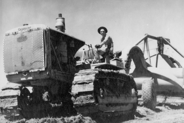Worker driving a large piece of farm equipment