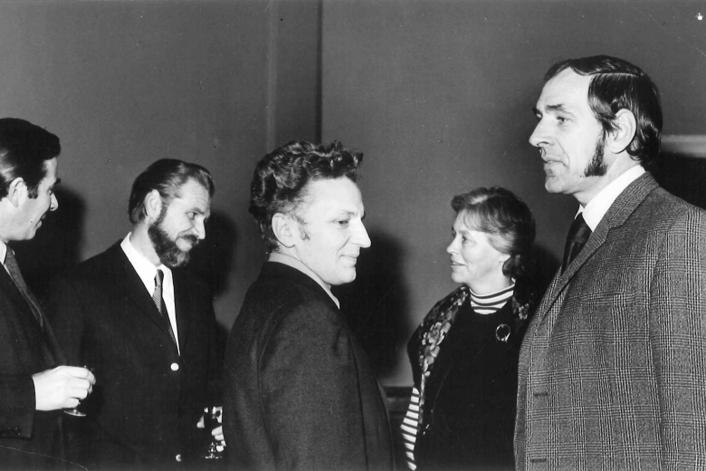 Four people stand in a room together, talking in pairs.