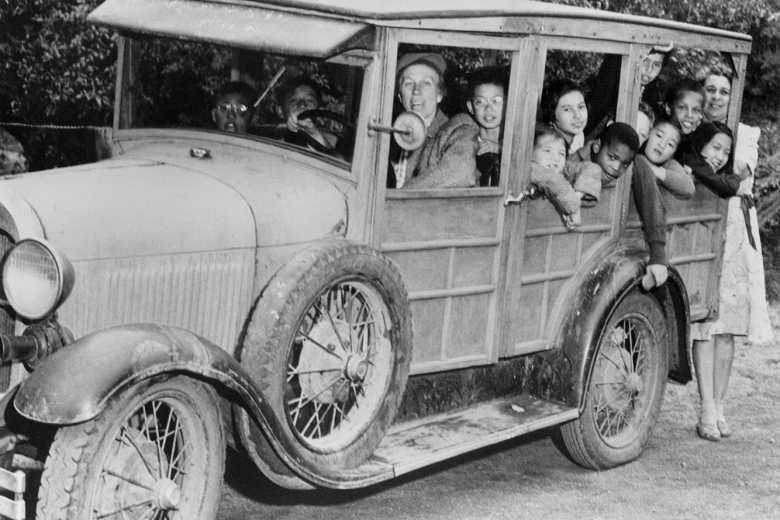 Car with children in the back, a man driving, and a woman standing behind.