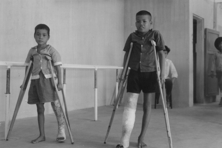 Two children with prosthetic legs walk with the aid of crutches.