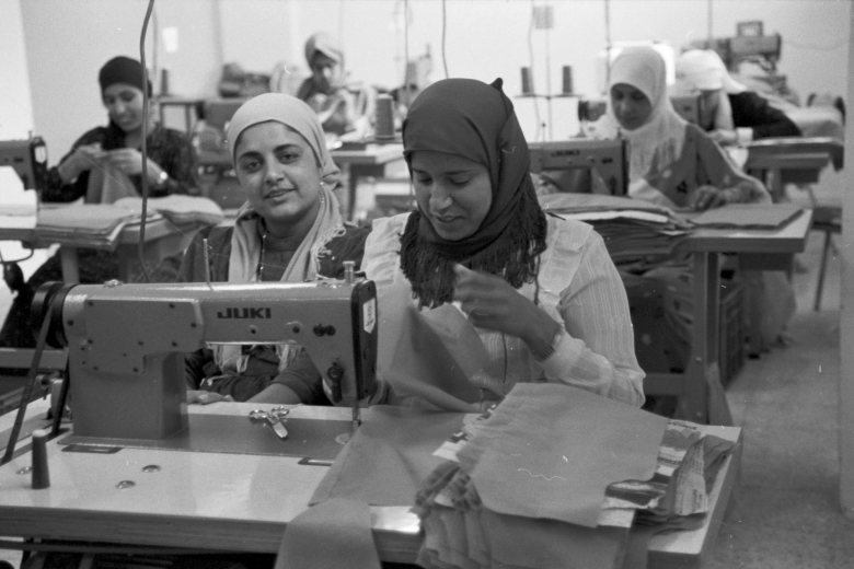 Women sew using sewing machines.