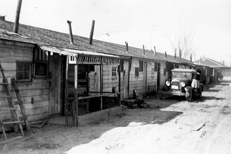 Row of wooden homes and one car
