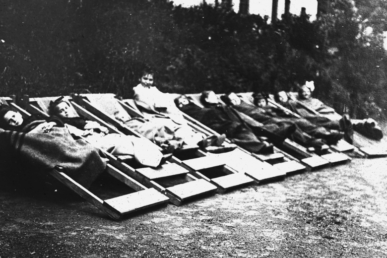 Row of children lying on wood cots.