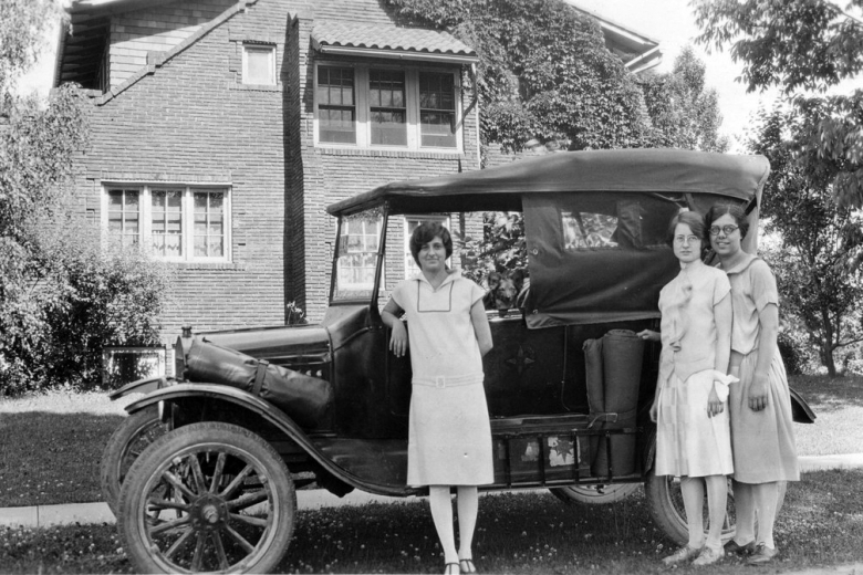 Three women in front of car.