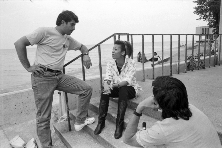 Two people sitting on steps speak with a man standing up.