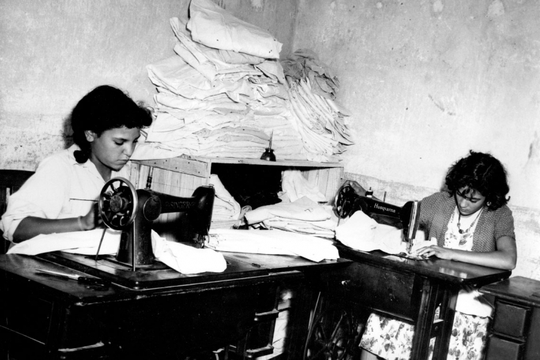 Two women work at sewing machines.