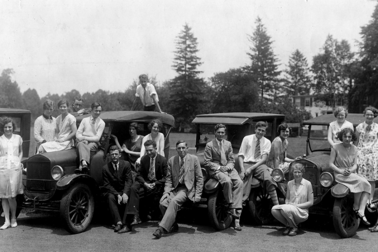 Men and women lined up in front of 1930s cars.