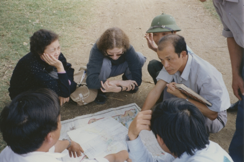 Six people engaged in conversation with maps and diagrams on the ground in front of them.