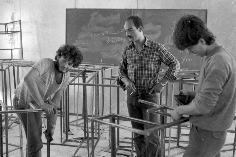 Two young men work on small construction projects in a classroom, overseen by an older man.