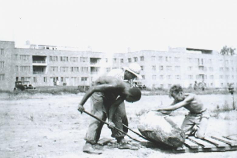 Three men work in empty lot, urban environment