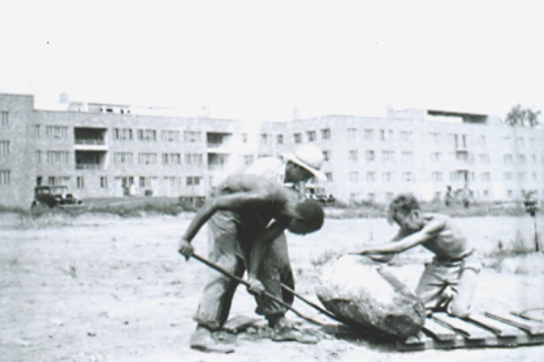 Three men work in empty lot, urban environment