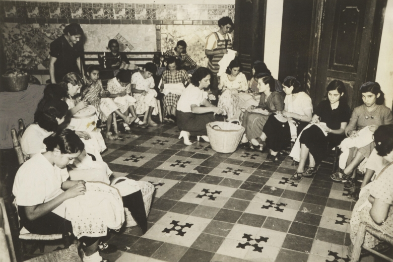 Group of women seated around a room, sewing by hand.
