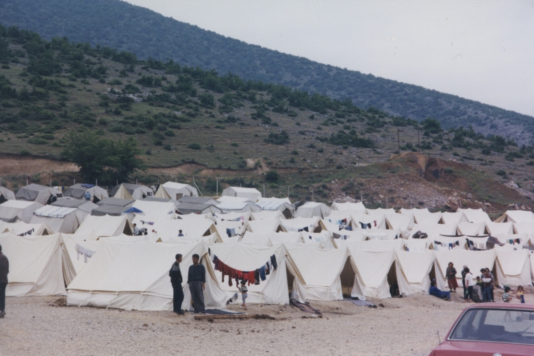 Large collection of refugee tents at the base of a hill, some with laundry drying on laundry lines strung between two tents.