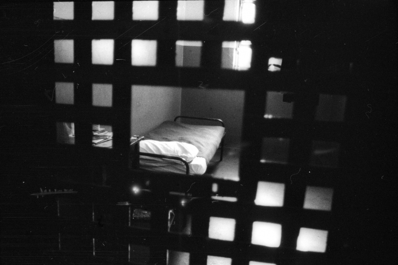 Photo through bars in a prison into a cell with a bed.