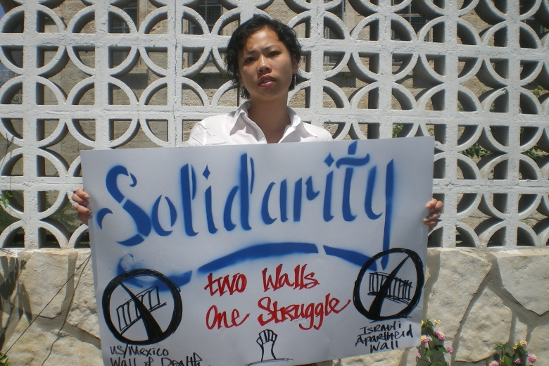 "Young woman holds a sign that reads ""Solidarity: two walls, one struggle."""