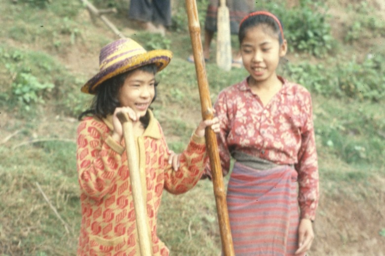 Two girls hold shovels, standing beside a body of water.