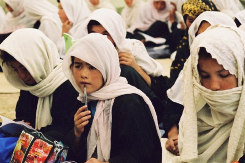 Young women sit together in lines, facing forward, one woman with a pen pressed up to her lip.