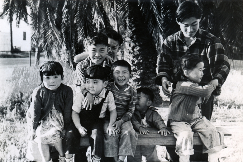 Group of children and a young adult sit on a bench under a palm tree
