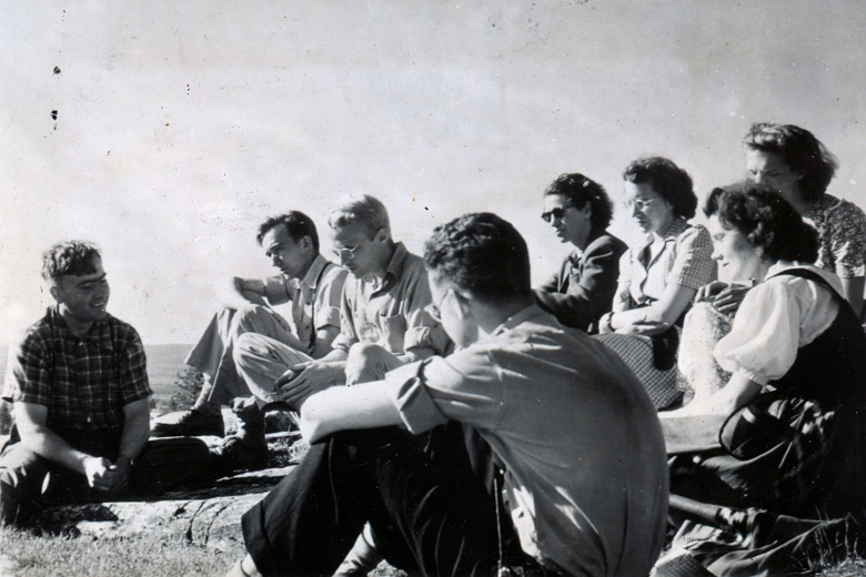 Young men and women sitting in a semi-circle facing one young man.