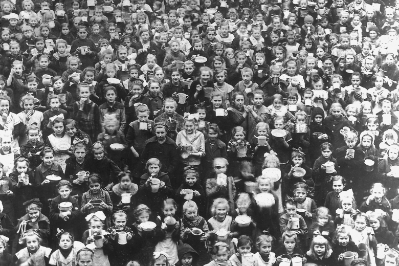 Enormous crowd of children holding bowls.