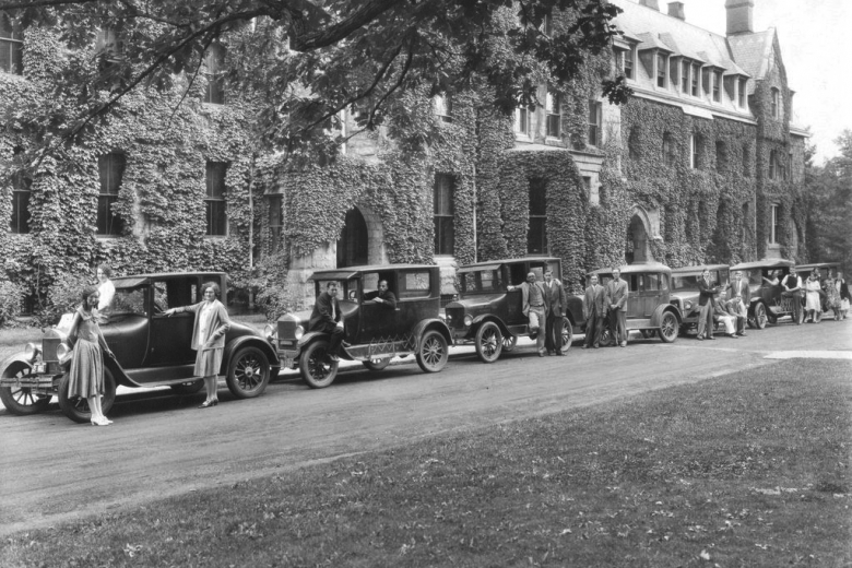 Long line of 1930s cars in front of ivy-covered buildings.