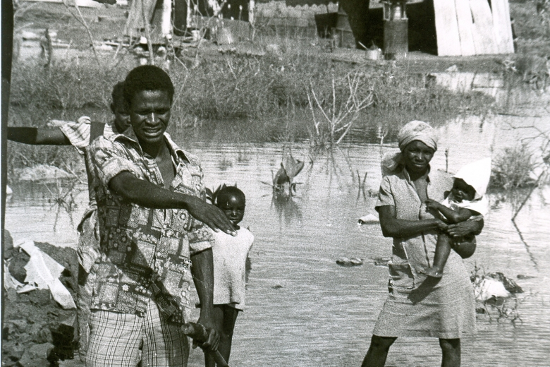 Woman holding a baby stands in water next to three other people, also standing in water.