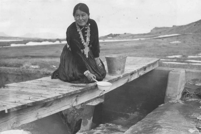 Navajo woman collecting water into bucket