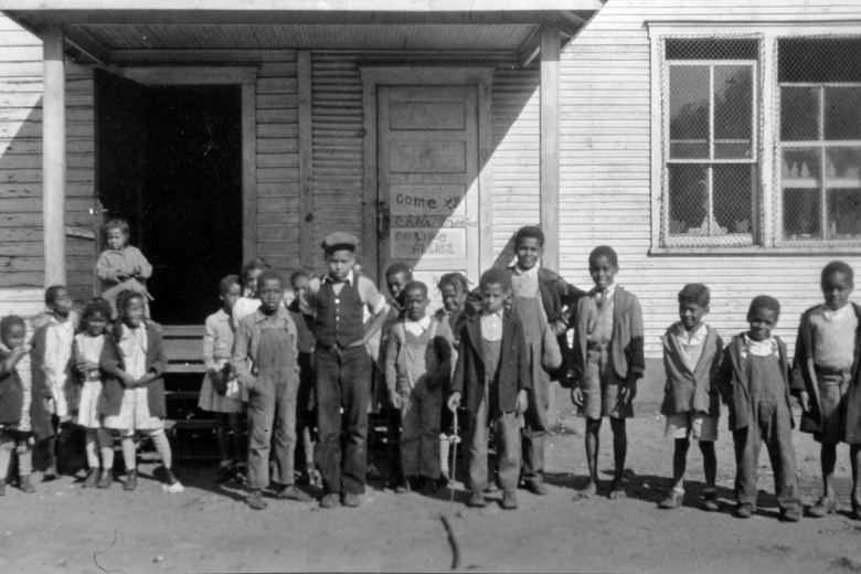 Group of 19 children standing outside a building with a front porch.
