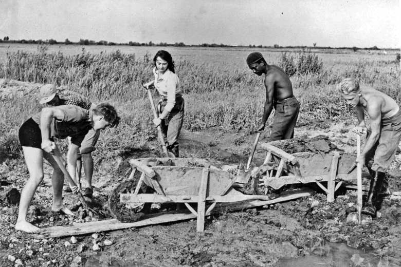 Young men and women of different races shovel soil into wooden wheelbarrows.