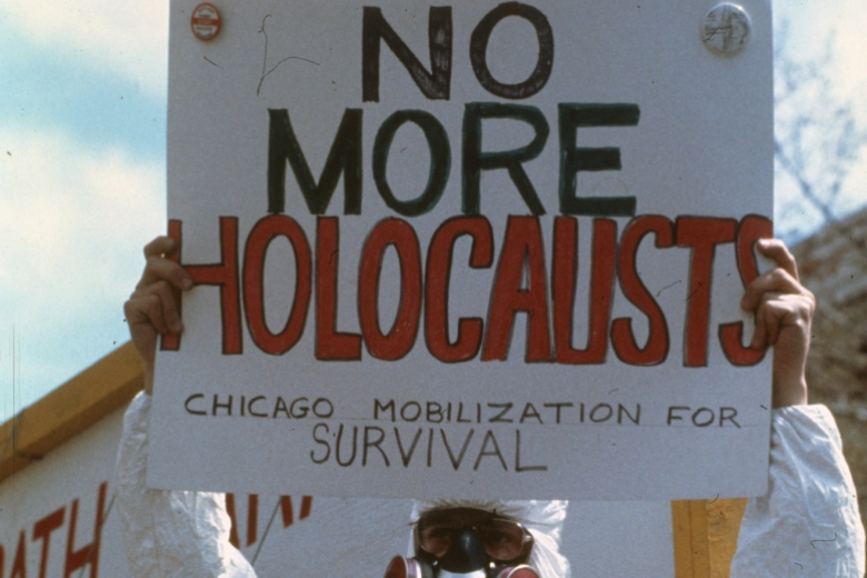 "A protester wearing a gas mask and a hazardous materials suit holds a sign that reads, ""No more Holocausts: Chicago mobilization for survival"""