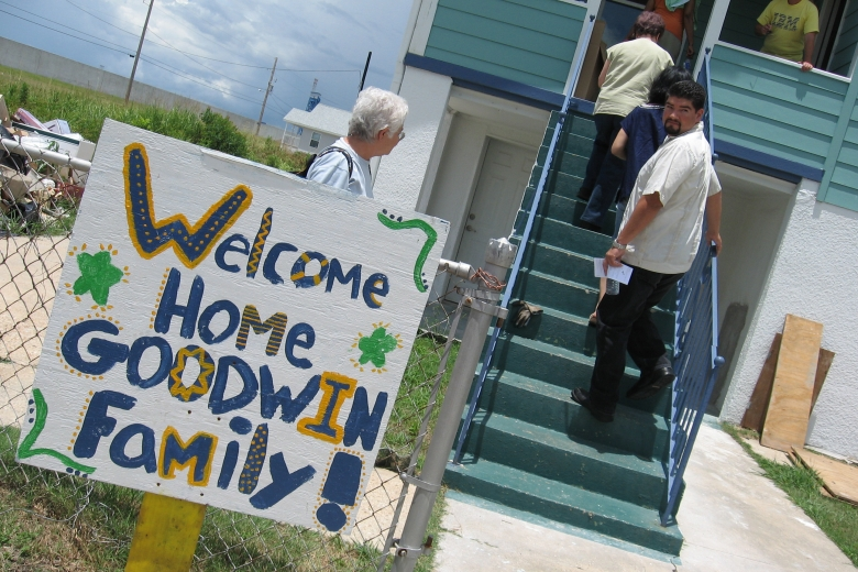 "Group of people climb stairs to a house with a sign in front that reads ""Welcome home, Goodwin Family!"""