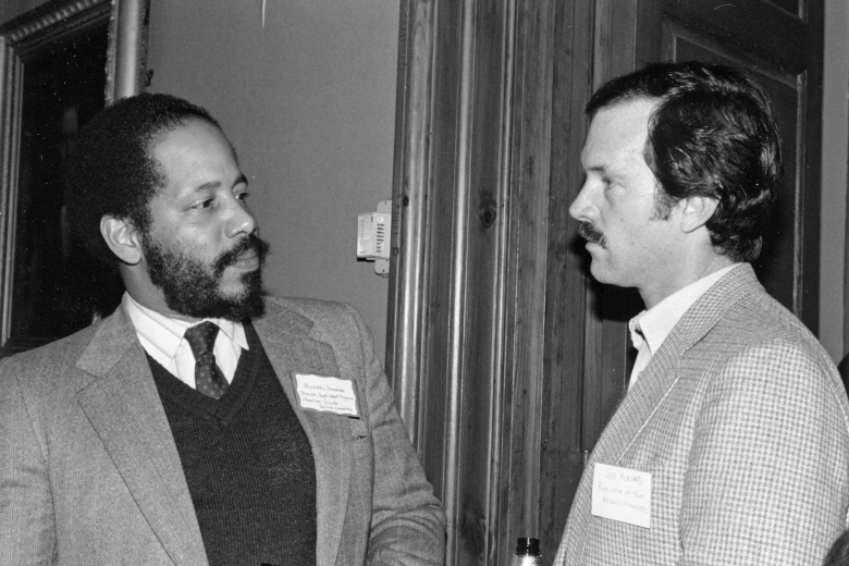 Two men with name tags stand in a room, talking to one another.