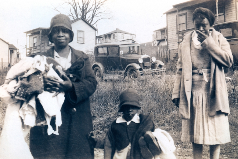 Two adult women and one child stand outside homes, holding clothing