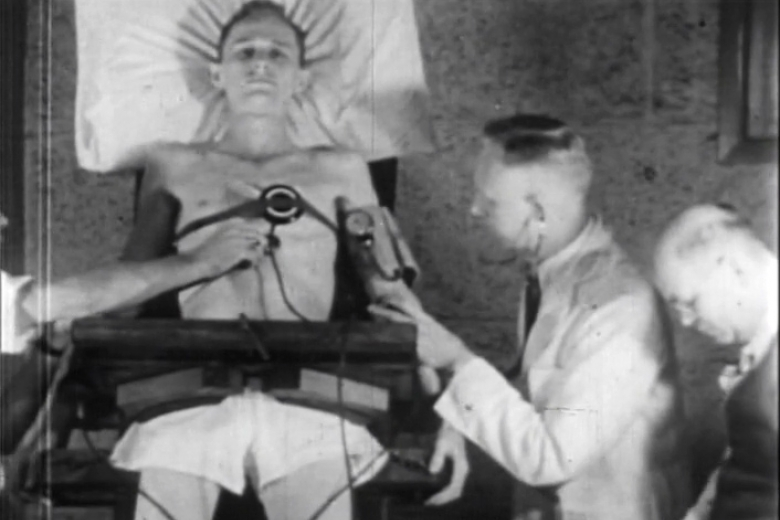 Young man lying on table surrounded by medical professionals with measuring implements