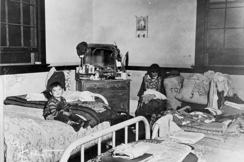 Child sitting on a bed in a room with several beds in it
