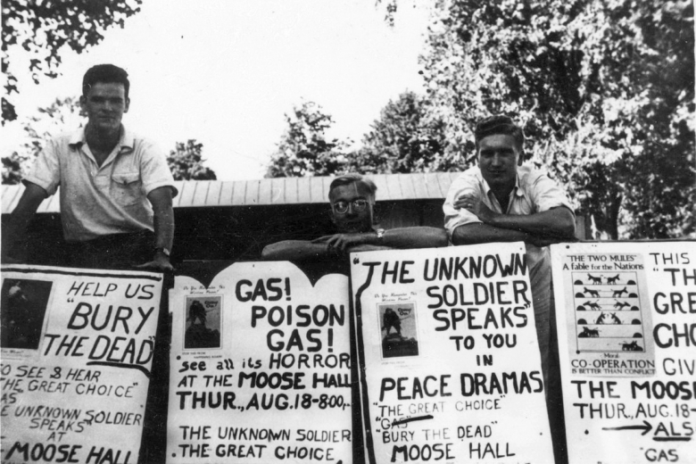 Men hold signs promoting a peace drama.