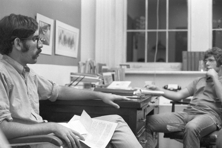 Two young men talk over a desk with papers on it.
