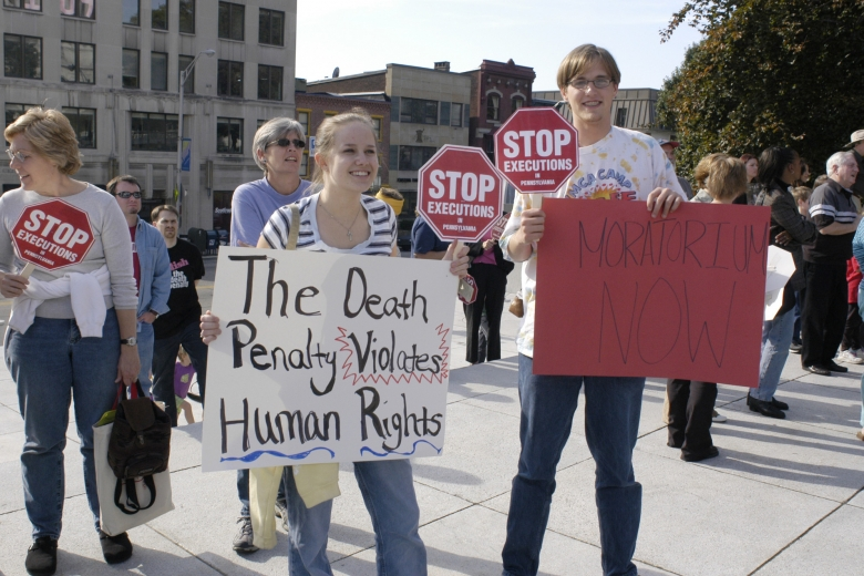 Demonstrators holding stop signs and other signs about ending the death penalty.