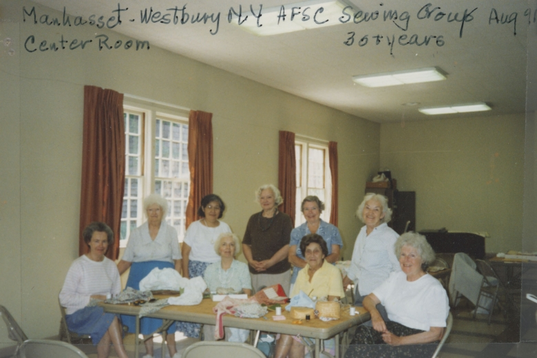 Nine elderly women stand and sit around a table covered with fabric and sewing supplies.