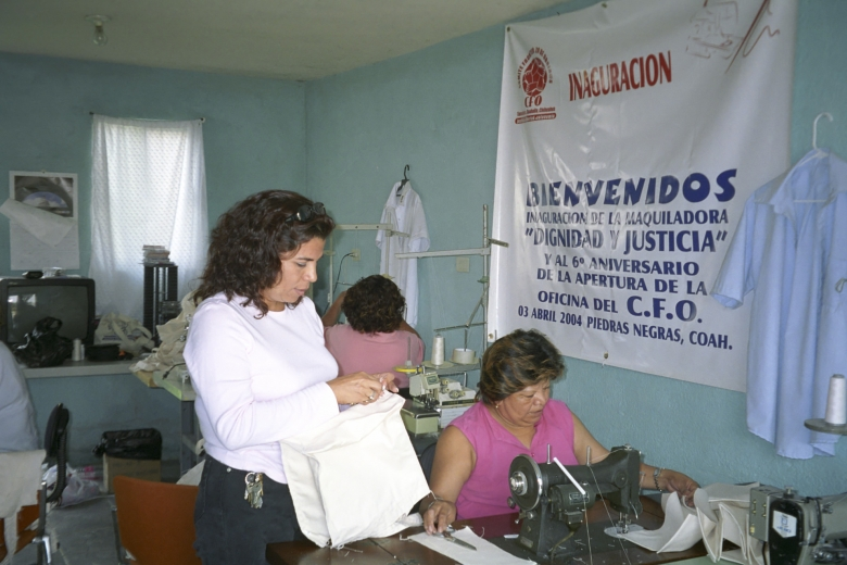 Women work with fabric, two sitting at sewing machines.