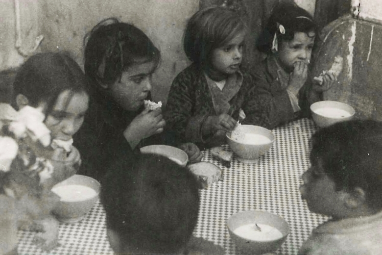 Children sitting at a table eating soup.