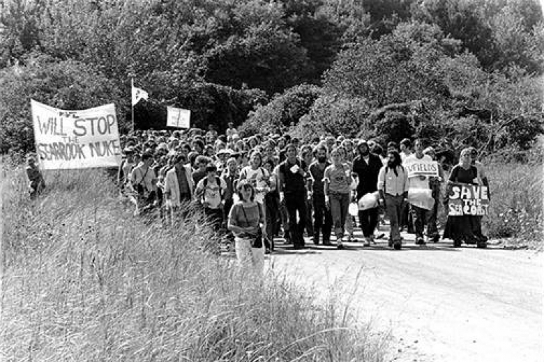 Group of protesters march together on a road through tall grass holding signs with messages against nuclear power plant construction